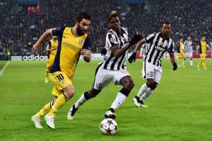 "Juventus' defender from France Patrice Evra (R) and Juventus' midfielder from France Paul Pogba (C) fights for the ball with Atletico Madrid's Turkish midfielder Arda Turan (L) during the UEFA Champions League football match Juventus vs Atletico Madrid at the ""Juventus Stadium"" in Turin on December 9, 2014.    AFP PHOTO / GIUSEPPE CACACE        (Photo credit should read GIUSEPPE CACACE/AFP/Getty Images)"